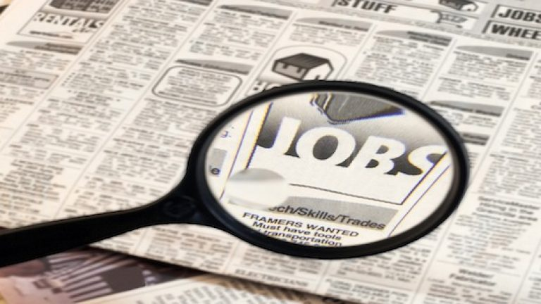 Newspaper opend to the want ads.  Magnifying glass highlighting the word Jobs.