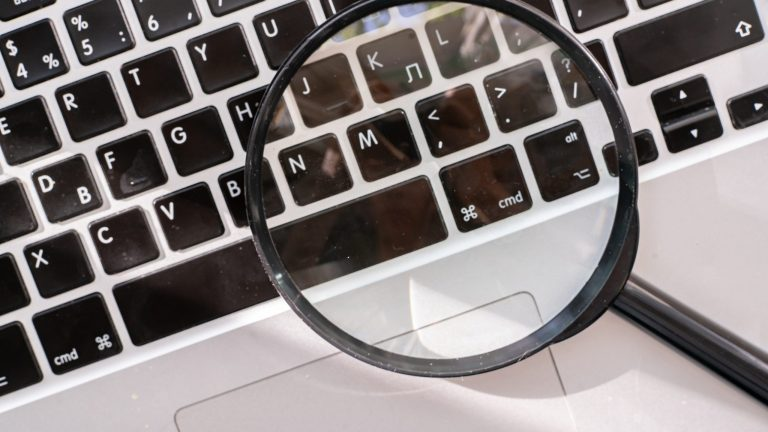 a magnifying glass on the keyboard, searching on the internet concept