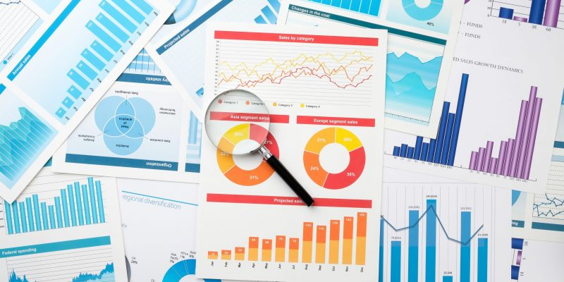 Business chart and magnifier on the table. Desktop of a businessman. The concept of highlighting key information in business.