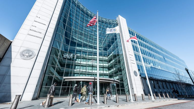 Washington DC, USA - January 13, 2018: US United States Securities and Exchange Commission SEC entrance, people walking, sign, entrance, american flag, looking up sky, glass windows reflection